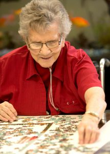 Woman putting puzzle together.