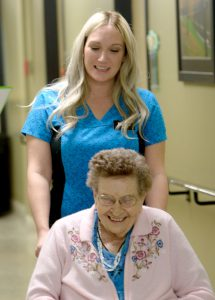 Woman in wheelchair with nurse.